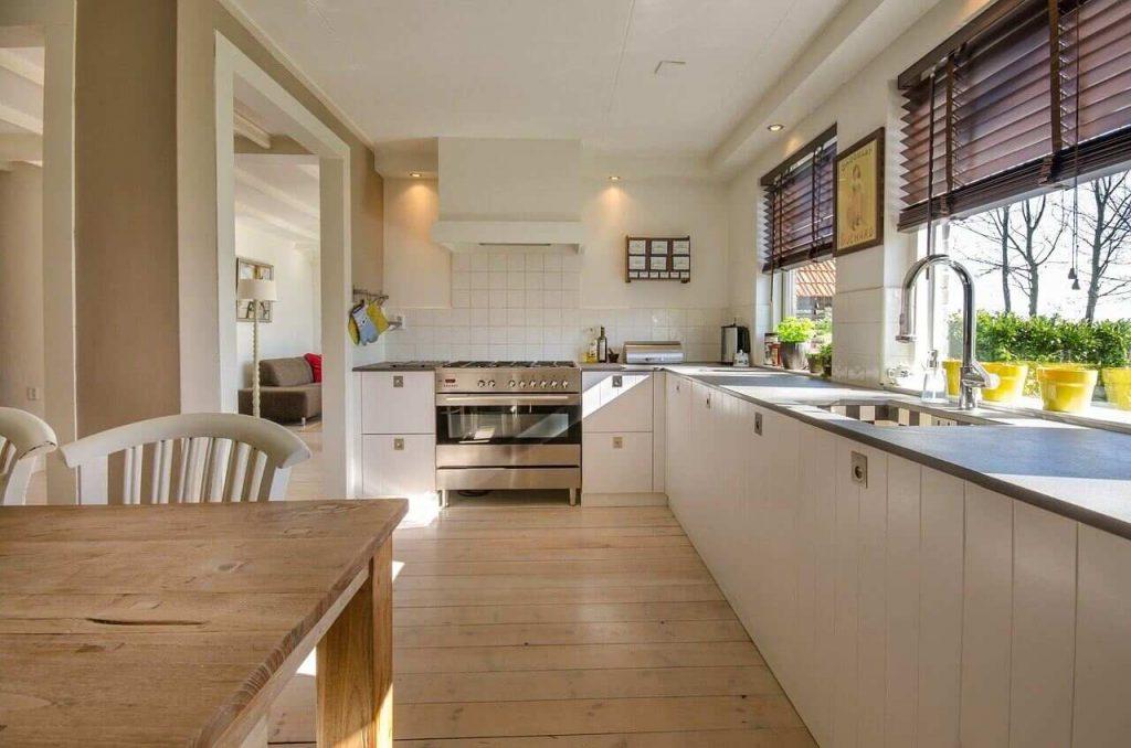 Cozinha planejada branca e bege com persianas escuras