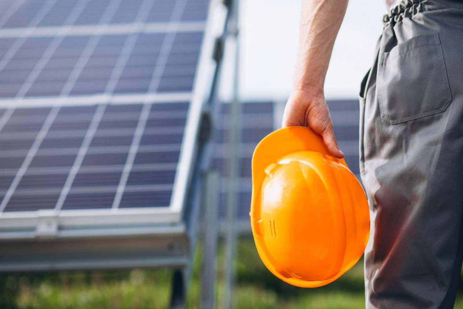 Homem segura capacete diante de painéis solares